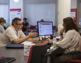 Un home realitza una consulta en una oficina de l'Habitatge.