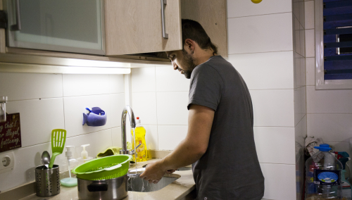 Un joven friega los platos en la cocina de su domicilio