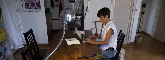 Una dona consulta l'ordinador portàtil a casa seva