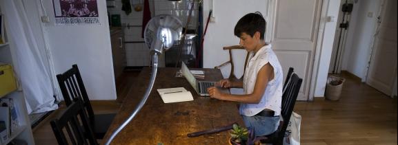 Una mujer consulta un ordenador portátil en su casa