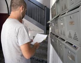 Un home mira el correu de la seva bústia