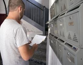 Un hombre mira el correo de su buzón