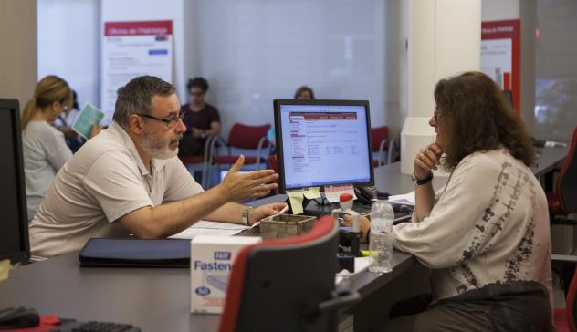 Una mujer realiza una consulta en una oficina municipal