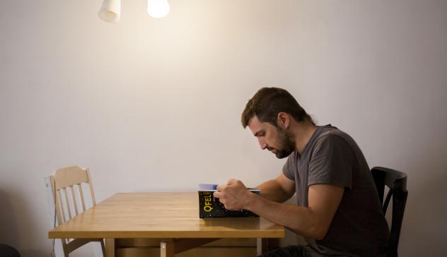 Un noi llegeix un llibre assegut a la taula del menjador