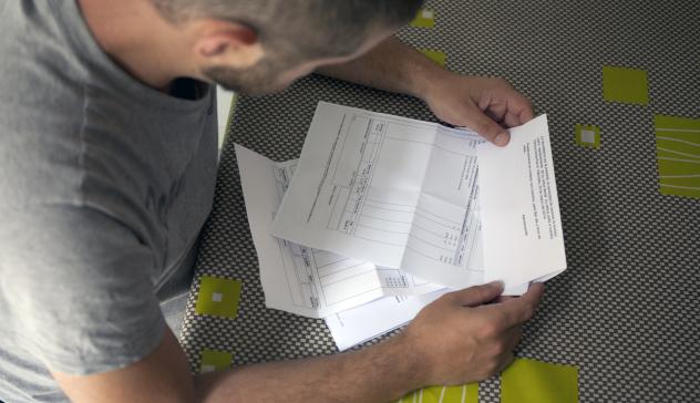 Un home consulta les seves factures