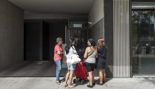 Un grupo de mujeres frente a la fachada de un edificio